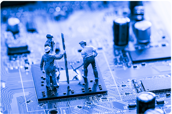 Three toy figurines atop a computer chip on a circuit board